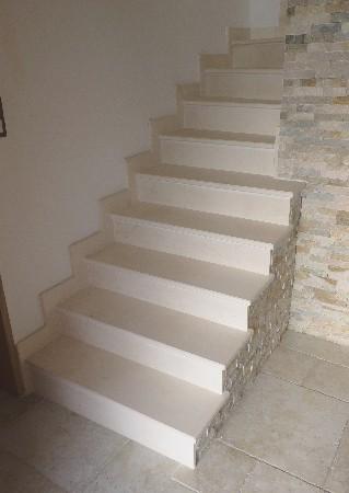 Revêtement d'un escalier quart tournant balancé en pierre de Lens. Marches, contremarches et plinthes.