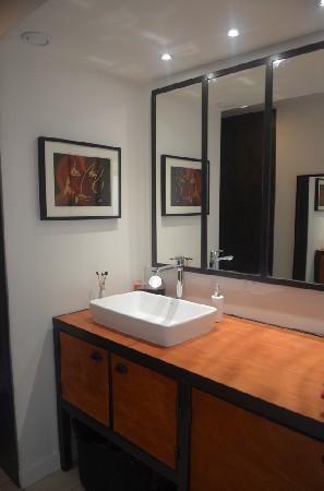 Meuble de salle de bain réalisé sur-mesure en bois et métal. Il sert de support pour la vasque et dispose d'un plan de travail ainsi que plusieurs espace de rangement. Idéal en association avec ce miroir verrière pour une touche résolument industrielle. hewel-mobilier.com