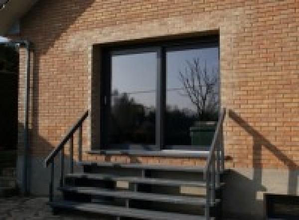 Perçage d'un mur porteur et pose d'une baie vitrée et d'un escalier extérieur.