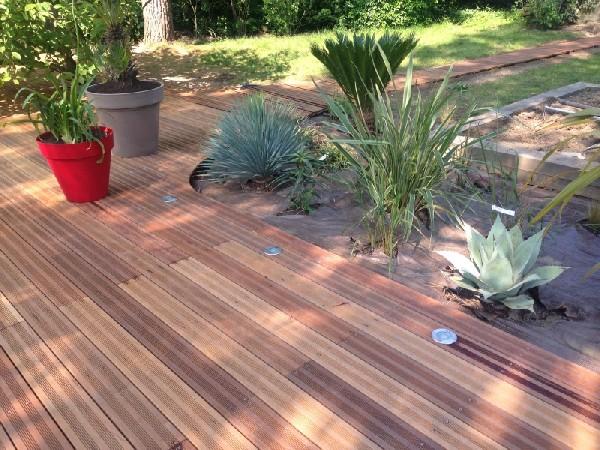 Terrasse en bois inscrustée de spot lumineux.